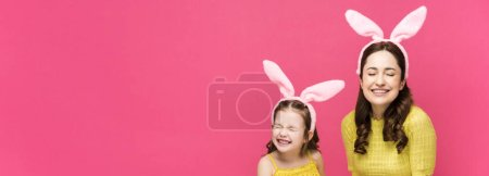Photo for Panoramic shot of happy mother and daughter in bunny ears holding easter eggs and laughing isolated on pink - Royalty Free Image