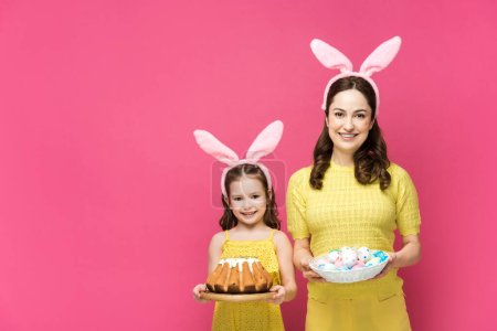 Photo for Happy mother in bunny ears holding painted chicken eggs near daughter with easter cake isolated on pink - Royalty Free Image