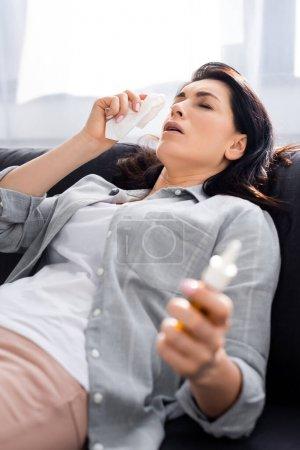 foyer sélectif de la femme allergique tenant la serviette et pulvérisation nasale tout en étant couché sur le canapé