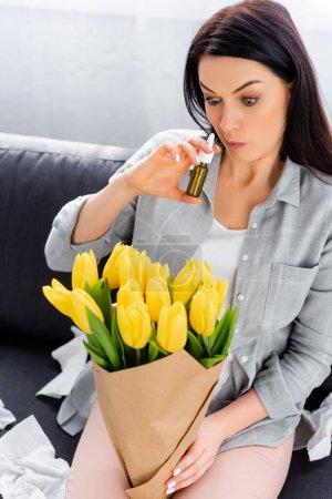 Photo pour Femme allergique au pollen assise sur un canapé avec des fleurs et tenant un spray nasal - image libre de droit