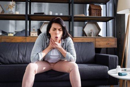 Frau mit geschlossenen Augen hustet während sie auf dem Sofa sitzt