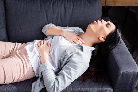 Asthmatische Frau hustet im Liegen auf Sofa