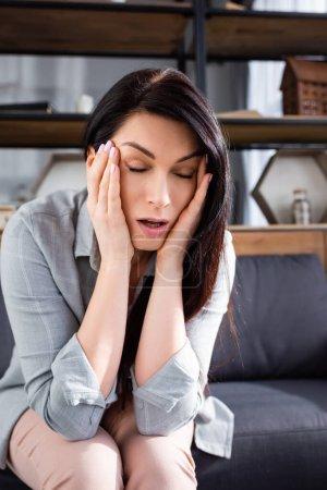 Frau mit Migräne berührt Schläfen im Sitzen auf Sofa