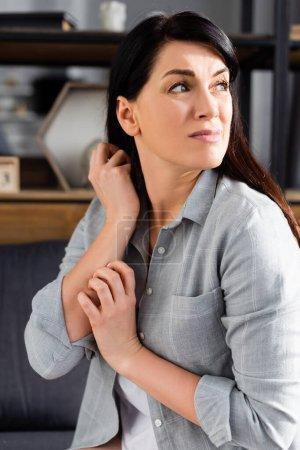 Allergische Frau kratzt sich beim Wegschauen die Hand