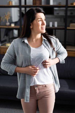 Photo pour Femme triste avec allergie qui gratte l'estomac à la maison - image libre de droit