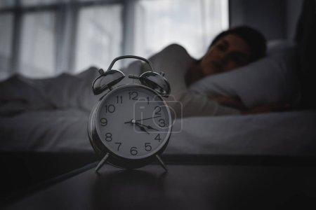Photo pour Focalisation sélective du réveil sur la table de chevet près de la femme éveillée - image libre de droit