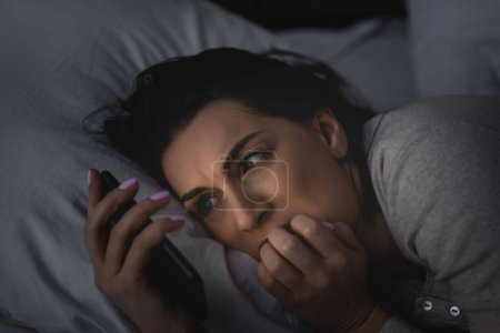 Photo for Scared woman with insomnia using smartphone in bedroom - Royalty Free Image