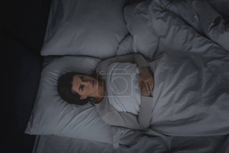 Photo pour Top view of woman with sleep disorder lying in bedroom - image libre de droit