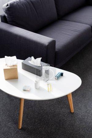 Photo pour Verre d'eau près de la boîte de tissu, inhalateur, plaquette thermoformée avec des pilules et un canapé - image libre de droit