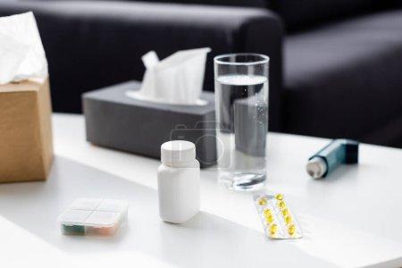 Photo pour Foyer sélectif de verre d'eau près de la boîte de tissu, inhalateur et plaquette thermoformée avec des pilules - image libre de droit