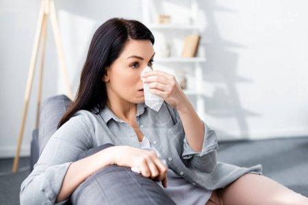 Photo pour Foyer sélectif de femme allergique éternuant et tenant des tissus dans le salon - image libre de droit
