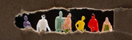 Photo pour Plan panoramique de carton avec trou et personnages isolés sur noir, concept d'égalité sociale - image libre de droit