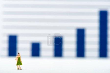 Photo pour Concentration sélective de la poupée sur la surface blanche avec des graphiques à l'arrière-plan, concept d'égalité - image libre de droit