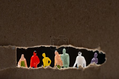 Photo pour Concentration sélective du carton avec trou et personnages isolés sur le noir, concept d'égalité sociale - image libre de droit