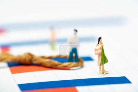 Photo pour Concentration sélective des personnages en plastique figures avec nœud sur les graphiques sur la surface blanche, concept d'égalité - image libre de droit