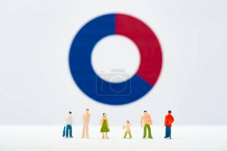 Photo pour Concentration sélective de la rangée de personnages sur une surface blanche avec un diagramme à l'arrière-plan, concept d'inégalité - image libre de droit