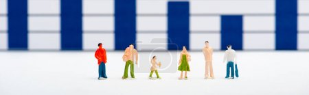 Photo pour Plan panoramique de personnages en plastique sur une surface blanche avec des graphiques bleus à l'arrière-plan, concept d'égalité - image libre de droit