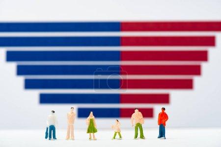 Photo pour Concentration sélective des personnages en plastique sur la surface blanche près de graphiques bleus et rouges à l'arrière-plan, concept d'égalité - image libre de droit