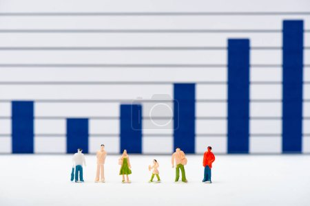 Photo pour Concentration sélective des personnages en plastique sur la surface blanche avec des graphiques bleus à l'arrière-plan, concept d'égalité - image libre de droit