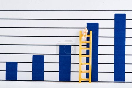 Photo pour Plastic people figure on ladder on white surface with blue analytics graphs at background, concept of equality - image libre de droit