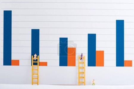 Photo pour Figures de personnes avec des échelles sur la surface blanche avec des graphiques en arrière-plan, concept d'égalité - image libre de droit