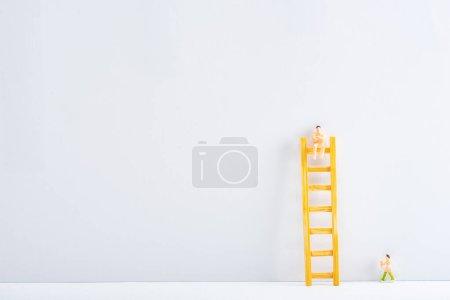 Photo pour Deux personnages avec échelle sur fond blanc sur fond gris, concept de droits à l'égalité - image libre de droit