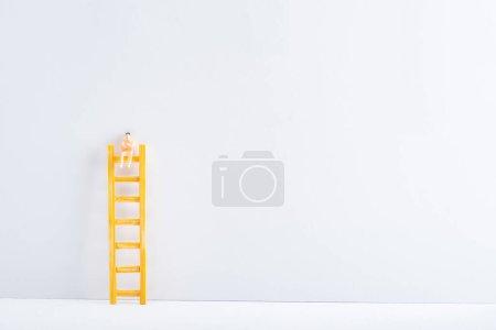 Photo pour Poupée sur échelle sur fond blanc sur fond gris, concept de droits à l'égalité - image libre de droit