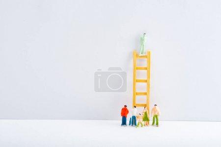 Photo pour Figures de personnes près de l'échelle avec jouet sur surface blanche sur fond gris, concept de droits à l'égalité - image libre de droit