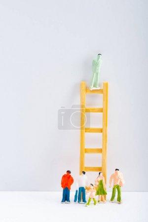 Photo pour Poupée sur échelle avec des personnages sur fond blanc sur fond gris, concept de droits à l'égalité - image libre de droit