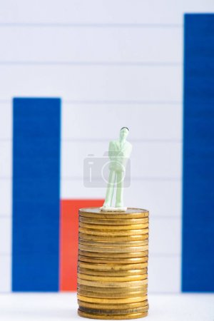 Photo for Concept of financial equality with people figure on stacked coins on white surface with graphs at background - Royalty Free Image