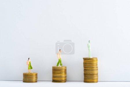 Foto de Las cifras de las personas sobre las monedas de superficie blanca sobre fondo gris, el concepto de igualdad financiera - Imagen libre de derechos