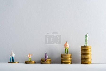Photo pour Figurines en plastique sur des pièces d'or empilées sur fond blanc sur fond gris, concept d'égalité financière - image libre de droit