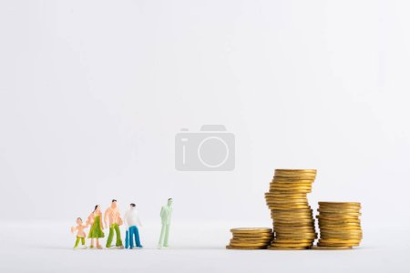 Photo for Toy people figures near stacked cons on white surface isolated on grey, concept of financial equality - Royalty Free Image
