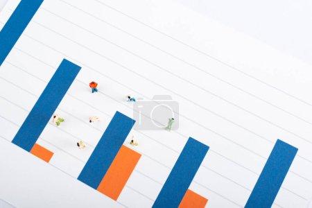 Photo pour Vue du dessus des figures de personnes sur la surface des graphiques bleus et rouges isolés sur blanc, concept d'égalité - image libre de droit