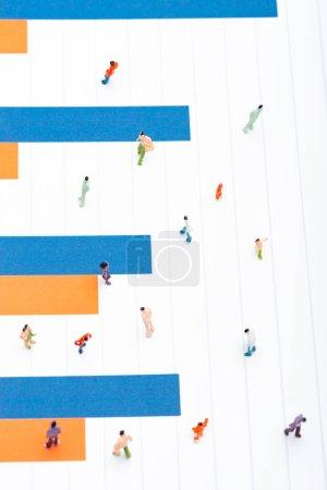 Photo pour Vue du dessus des personnages en plastique sur la surface avec des graphiques en bleu et orange, concept d'égalité - image libre de droit