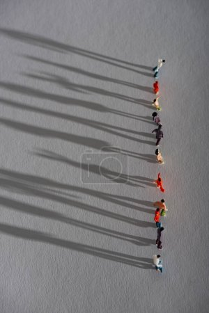 Photo for Top view of row of plastic people figures with shadow on gray surface - Royalty Free Image