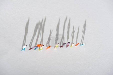 Photo pour Vue du dessus de la rangée de personnages en plastique figures sur la surface blanche avec ombre - image libre de droit