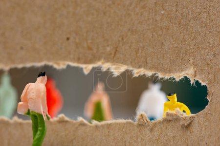 Photo pour Concentration sélective des personnages figure près du trou dans le carton avec des silhouettes de jouets en arrière-plan - image libre de droit