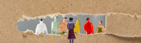 Photo for Concept of social rights with people figures near hole in cardboard isolated on grey, panoramic shot - Royalty Free Image