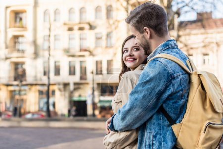 Girl and man hugging, smiling and looking at each other in city