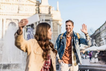 Selective focus of woman with boyfriend waving hand taking selfie with smartphone near fountain in city