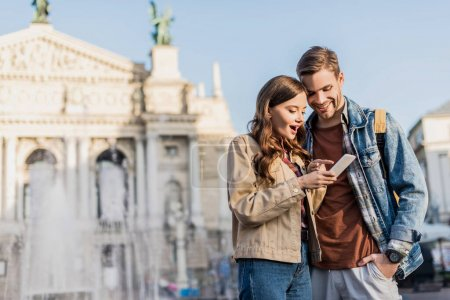 Happy and excited couple using smartphone in city