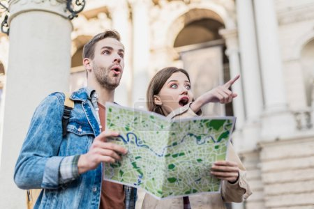 Low angle view of excited girlfriend pointing with finger and boyfriend holding map together in city