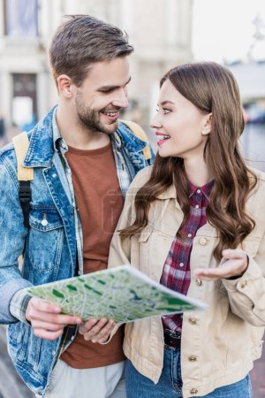 Photo for Selective focus of boyfriend and girlfriend looking at each other, smiling and holding map - Royalty Free Image