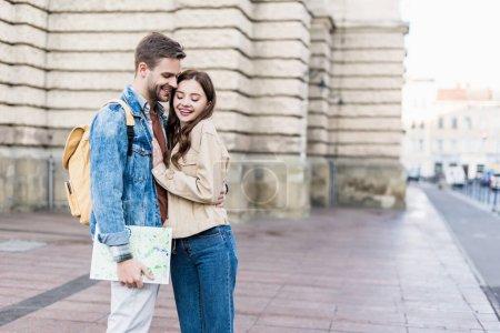 Photo pour Focus sélectif de couple heureux serrant et souriant avec la carte dans la ville - image libre de droit