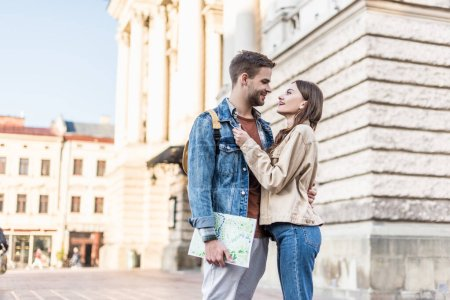 Photo for Selective focus of happy couple hugging and looking at each other with map in city - Royalty Free Image