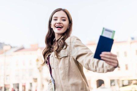 Photo pour Vue à angle bas d'une belle femme excitée montrant son passeport avec un billet d'avion - image libre de droit