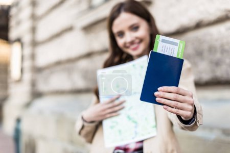 Photo for Selective focus of woman smiling, holding map and showing passport with air ticket - Royalty Free Image