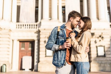 Boyfriend and girlfriend with disposable cups of coffee hugging in city