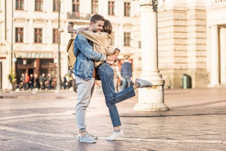 Boyfriend and girlfriend holding disposable cups of coffee and hugging in city